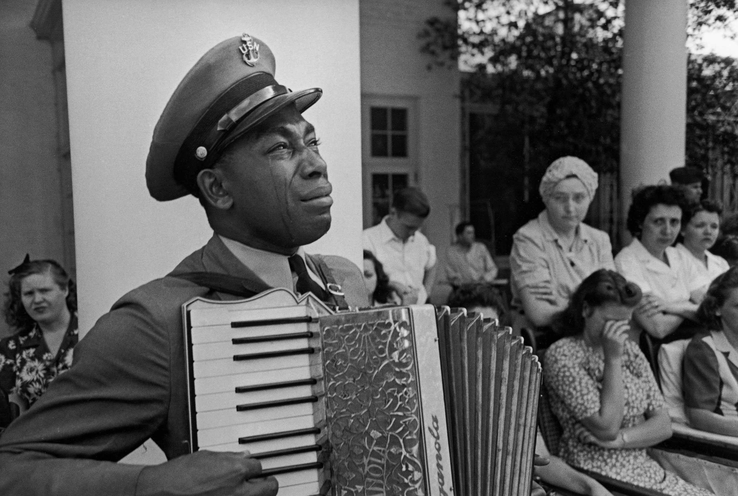 Navy CPO Graham Jackson with tears of grief streaming down his cheeks as he plays 'Goin' Home' on the accordion while Pres. Franklin D. Roosevelt's body is carried from the Warm Springs Foundation where he died suddenly on April 12, of a stroke.