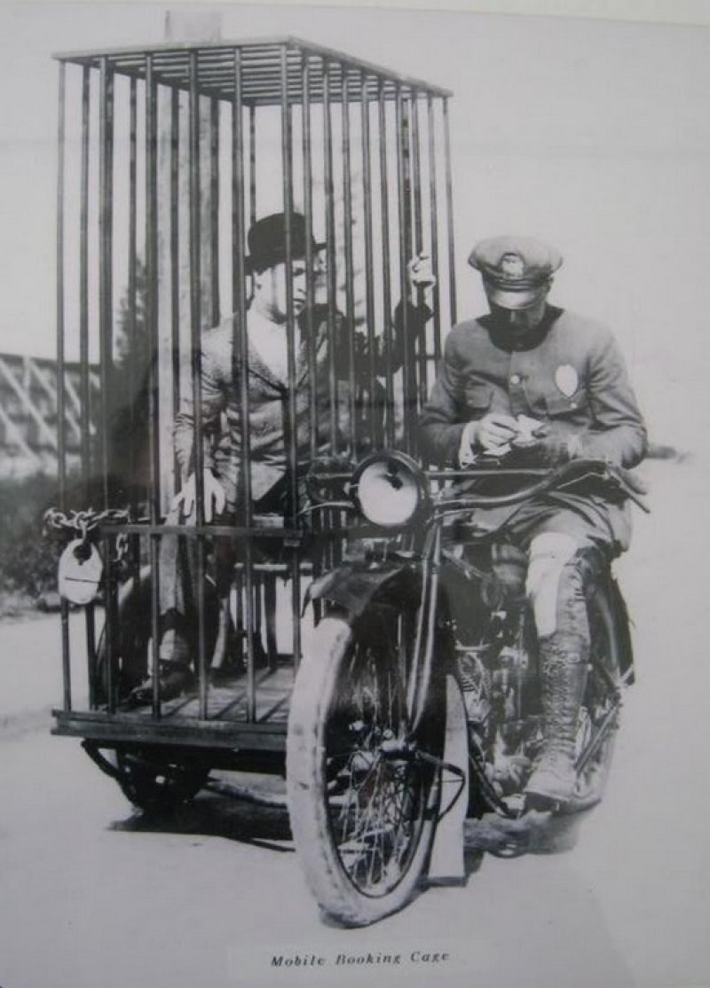 a-police-officer-on-a-harley-and-an-old-fashioned-mobile-holding-cell-1921