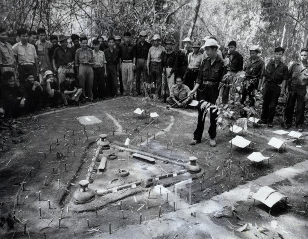 03 Oct 1964, South Vietnam --- A Vietcong guerrilla points to a model of the Ben Cau fortress near Tay Ninh during a briefing for an attack during the Vietnam War. --- Image by © Bettmann/CORBIS