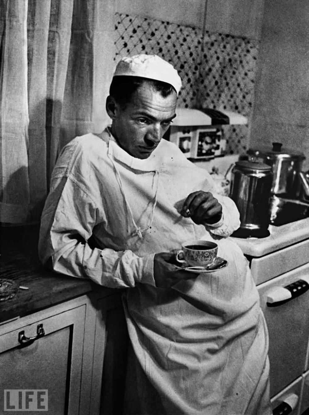 "Dr. Ernest Ceriani, the subject of a 1948 Life magazine story titled ""Country Doctor,"" pauses after a long surgery."