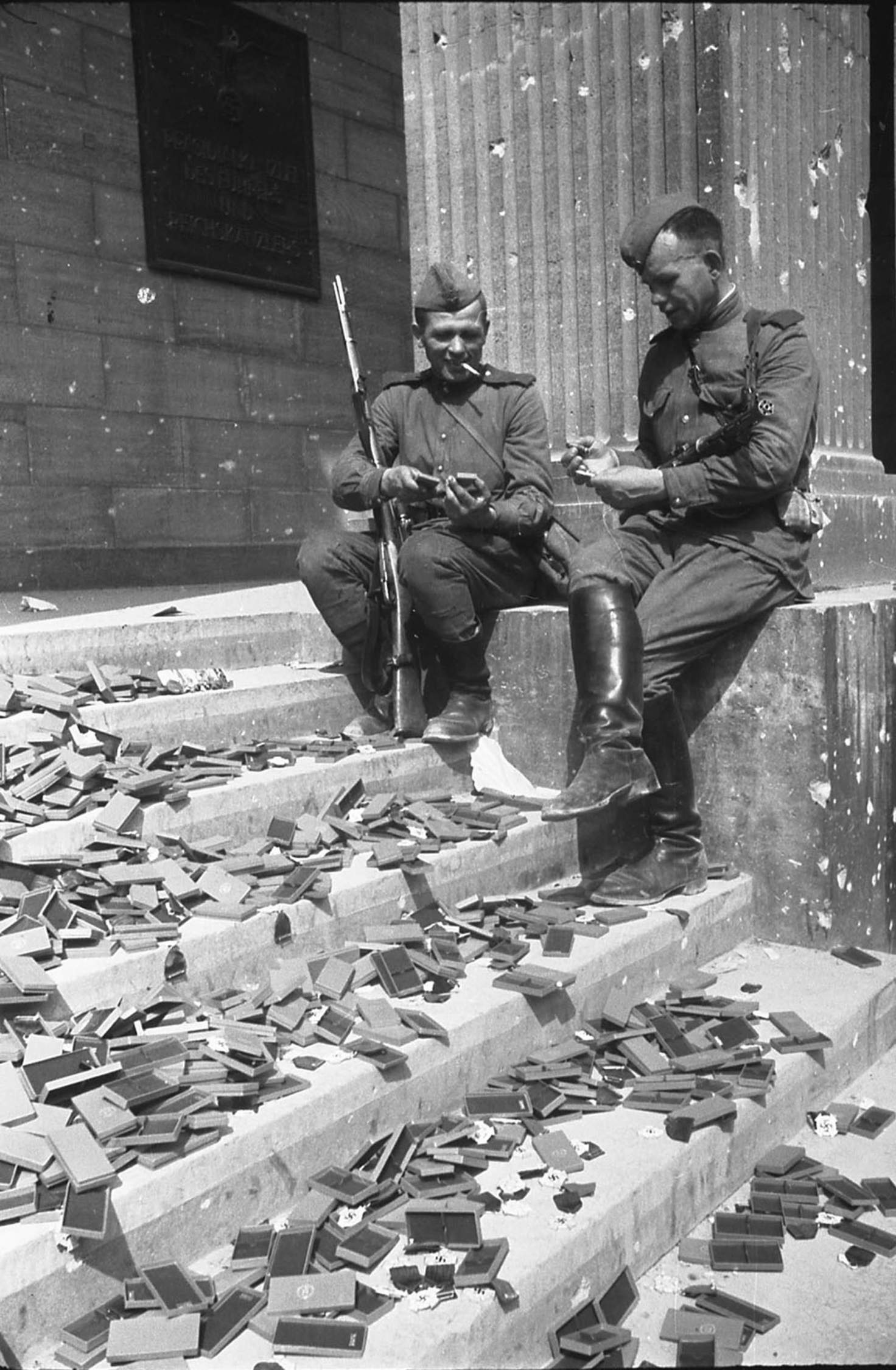 Russian Soldiers on the steps of the Reich Chancellery looking at German medals that would never be awarded, 1945