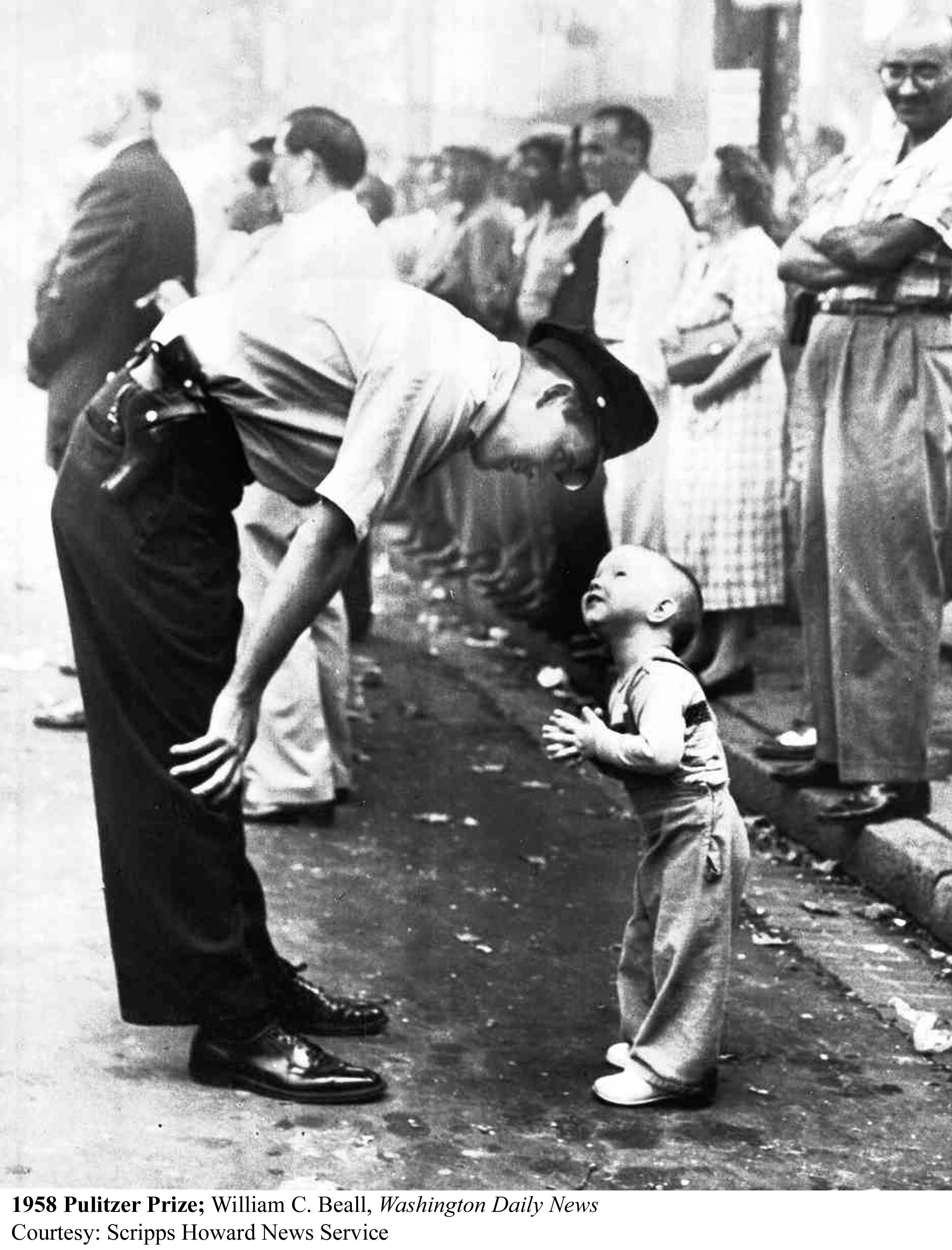 a-policeman-patiently-reasoning-with-a-two-year-old-boy-trying-to-cross-a-parade-1958