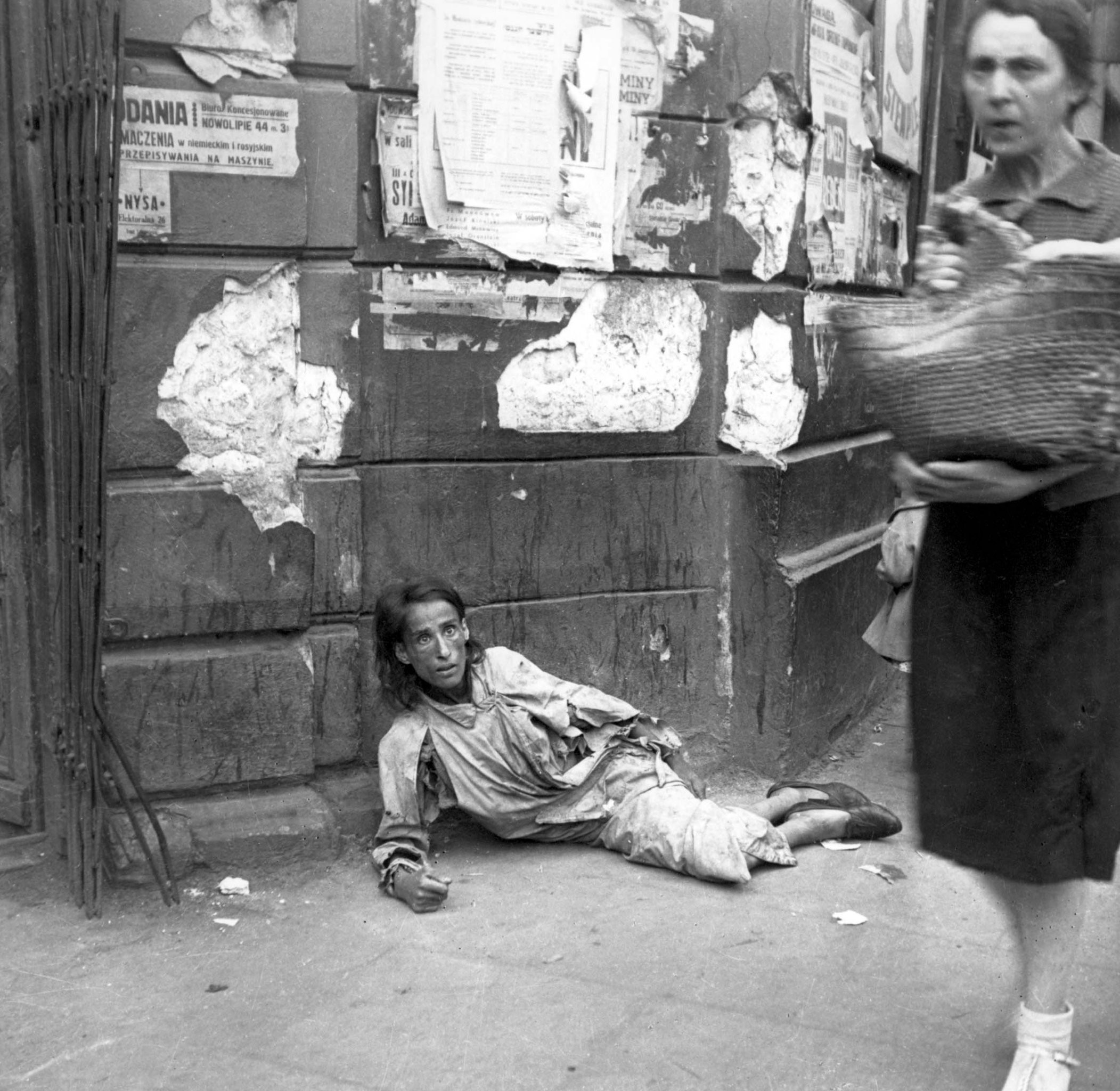 a-woman-lying-on-the-pavement-in-the-warsaw-ghetto-starving-to-death-1941